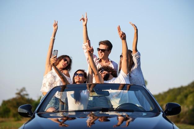 Giovani ragazze e ragazzi fortunati in occhiali da sole sono seduti in una cabriolet nera sulla strada alzando le mani e facendo selfie in una giornata di sole. .