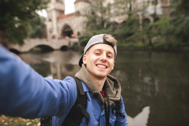 Il giovane turista fortunato fa un sephi sul lago e sul castello e sorride.