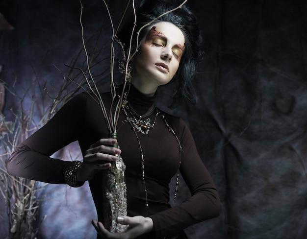 Giovane donna di lusso con trucco luminoso che tiene un mazzo di twi secco