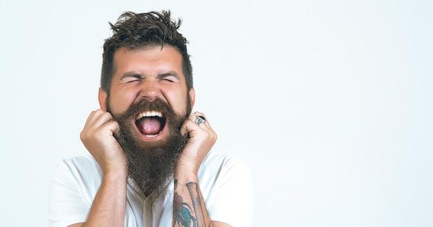 Giovane pazzo, viso espressivo, spaventato pos. ritratto ha sottolineato e urlando pazzo bell'uomo barbuto che indossa la maglietta bianca su sfondo bianco muro. nervi al limite quando la barba è graffiata