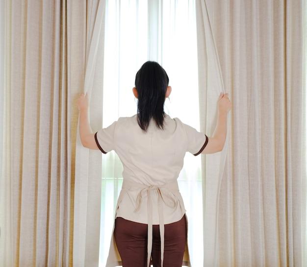 Giovane cameriera che apre le tende nella stanza d'albergo Foto Premium