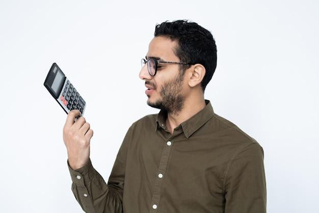 Ragioniere maschio giovane o studente in occhiali guardando la calcolatrice in mano con espressione insoddisfatta