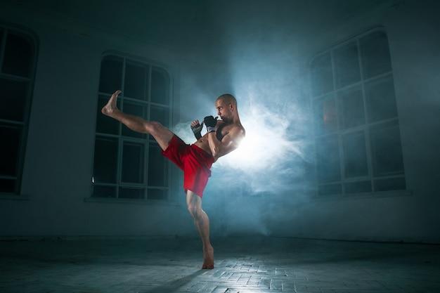 Il giovane atleta maschio che fa kickboxing su uno sfondo di fumo blu