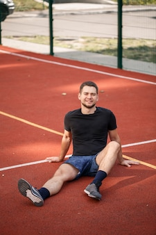 Un giovane atleta maschio con la barba si siede su un campo da tennis rosso. bel ragazzo in maglietta e pantaloncini