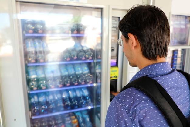Giovane turista maschio viaggiatore con zaino e sacco a pelo che sceglie uno spuntino o una bevanda al distributore automatico