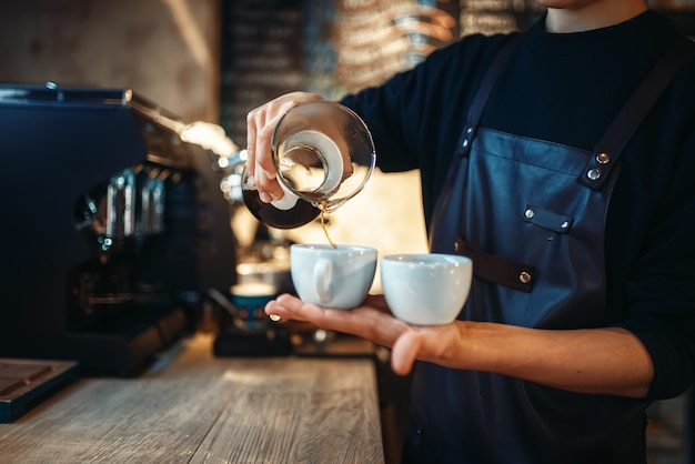 Il giovane barista maschio tiene due tazze di caffè fresco