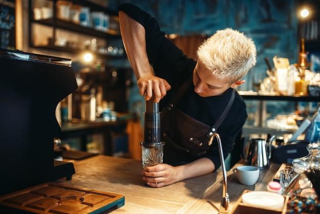 Il giovane barista maschio fa il caffè espresso fresco