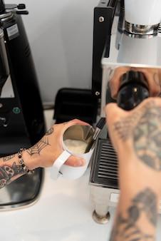 Giovane barista maschio con tatuaggi che usa la macchina del caffè al lavoro