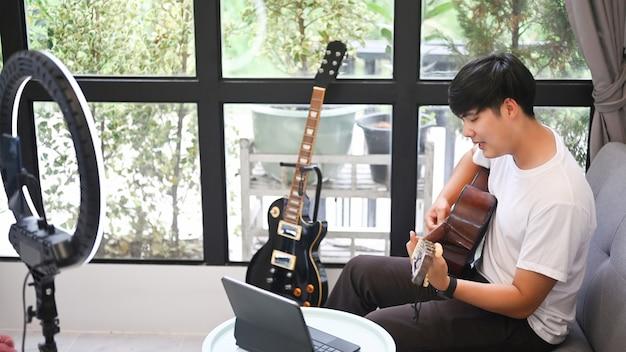 Giovane blogger maschio che suona la chitarra e registra video a casa.