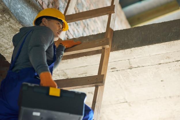 Giovane costruttore maschio in tuta blu e elmetto che sembra concentrato salendo la scala