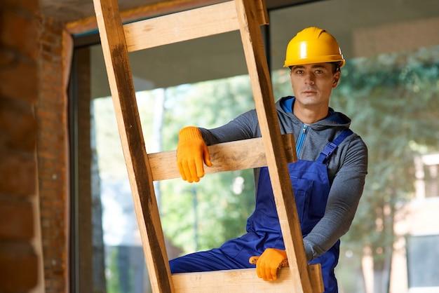 Giovane costruttore maschio in tuta e elmetto che guarda l'obbiettivo, salendo la scala mentre lavora al cantiere del cottage