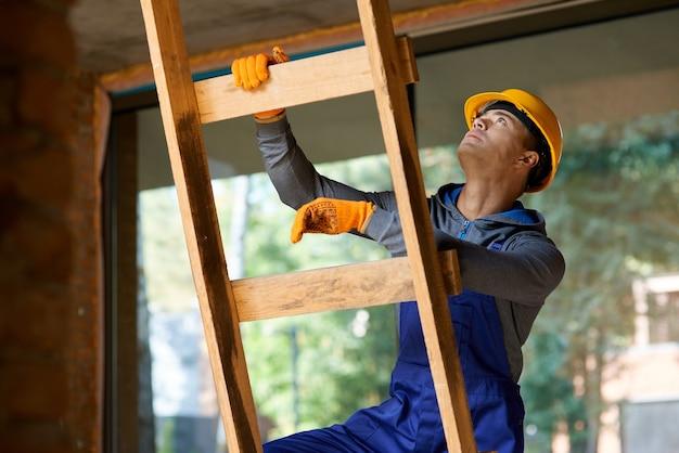 Giovane costruttore maschio in tuta e elmetto che sembra concentrato, salendo la scala