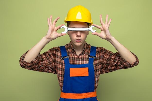Giovane costruttore maschio che indossa l'uniforme che tiene e il viso coperto con una chiave a forchetta