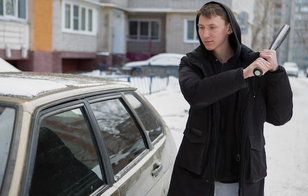 Un giovane bullo maschio con una mazza da baseball tenta di rompere un finestrino della macchina