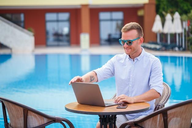 Il giovane uomo d'affari maschio in occhiali da sole lavora a un computer portatile seduto a un tavolo vicino alla piscina. lavoro a distanza. libero professionista