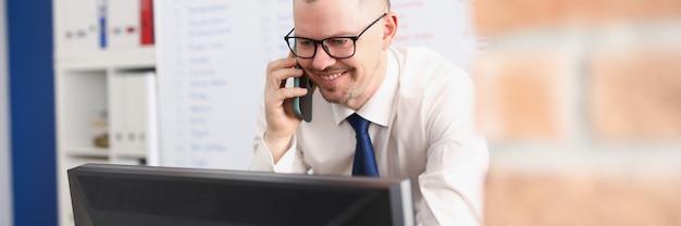 Giovane uomo d'affari maschio che parla sullo smartphone e guarda il monitor alla sua scrivania