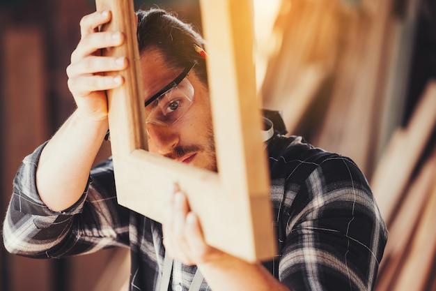 Un giovane falegname maschio che lavora nel complesso equivale a una barra di legno con una fresatrice in officina,