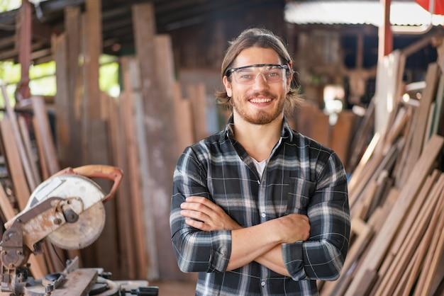 Il giovane falegname maschio indossa occhiali di sicurezza sorridenti con le braccia incrociate che lavorano nel laboratorio di falegnameria