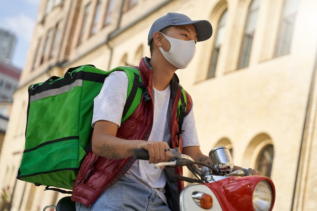 Giovane corriere maschio con borsa termica che indossa una maschera protettiva per il viso