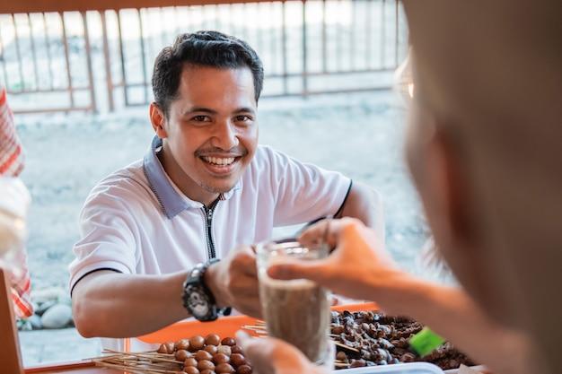 I giovani clienti maschi sorridono quando ricevono un bicchiere di caffè da un venditore in una bancarella del carrello