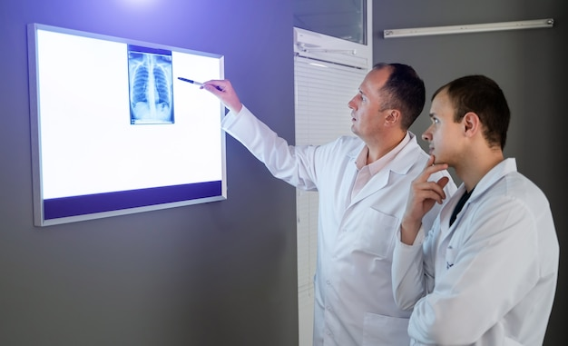 Giovani medici maschi che esaminano attentamente i raggi x e discutono la diagnosi.