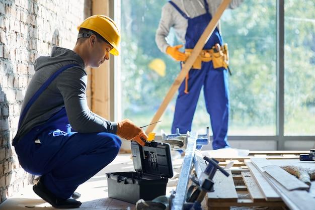 Giovane ingegnere maschio che prende lo strumento dalla cassetta degli attrezzi mentre lavora al cantiere del cottage