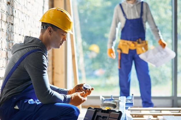 Giovane ingegnere maschio che lavora al cantiere del cottage, raccogliendo nastro adesivo dalla cassetta degli attrezzi