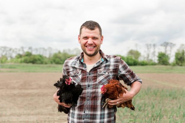Un giovane agricoltore maschio con un pollo in mano si trova nel suo giardino nel villaggio.