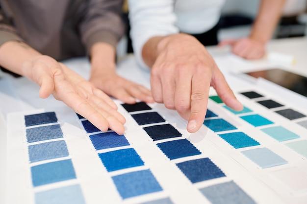 Giovani stilisti maschi e femmine che puntano a campioni di colore di tessuto e scegliendone uno per il nuovo ordine del cliente