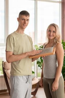 Giovane maschio fitness e istruttore di yoga con massaggio pad e bionda sportiva in activewear in piedi davanti alla telecamera