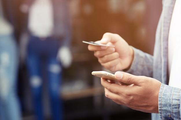 Mani maschii giovani che tengono la carta di credito e usando il telefono astuto mobile