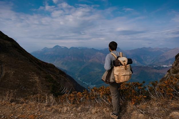 Giovane maschio hipster in montagna in autunno. concetto di destinazione di viaggio di scoperta. turista sullo sfondo di alte rocce. sport e concetto di vita attiva.