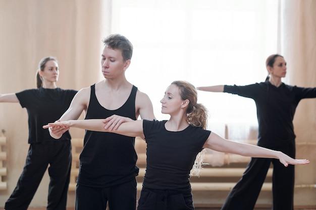 Giovane maschio istruttore di danza aiutando una delle femmine con le braccia tese durante l'allenamento in studio moderno