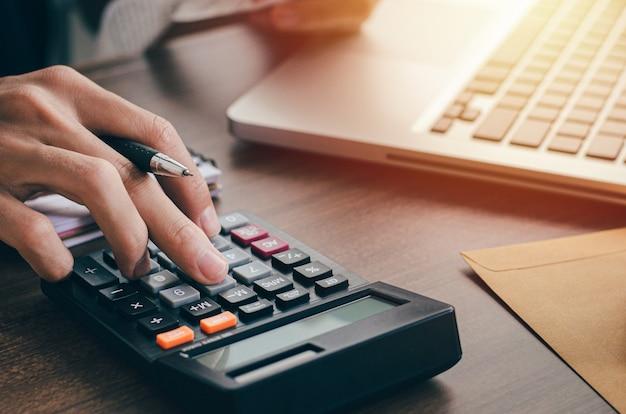 Giovane investitore maschio che calcola i costi di investimento con una calcolatrice e tiene in mano le banconote. con affari, investimenti, tasse
