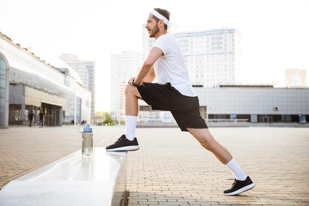 Giovane atleta maschio pareggiatore formazione e facendo allenamento all'aperto in città.