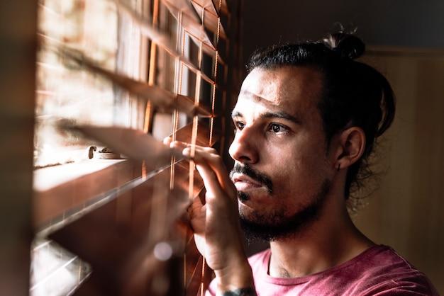 Un giovane maschio che guarda attraverso i ciechi della finestra per stare al sicuro durante l'epidemia di coronavirus