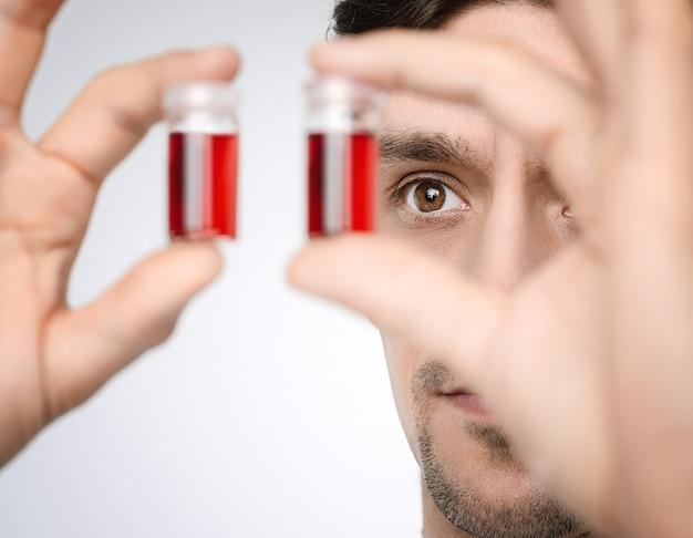 Il giovane medico o ricercatore maschio sostiene i campioni liquidi