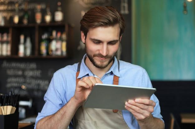 Giovane proprietario maschio che utilizza tablet digitale mentre si sta in piedi nella caffetteria.