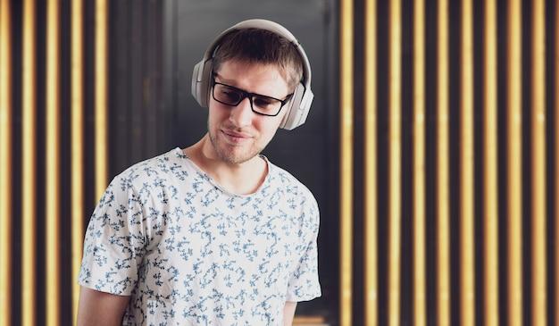 Un giovane maschio ascolta le cuffie e si gode l'audio rilassarsi e rilassarsi