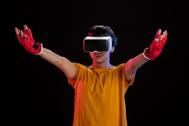 Giovane maschio che gioca la realtà virtuale in guanti di mma sulla superficie scura
