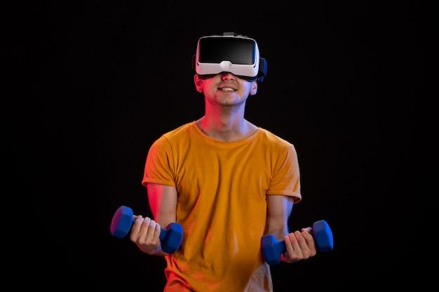 Giovane maschio che gioca la realtà virtuale con manubri sulla superficie scura