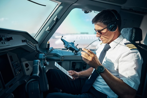 Il giovane professionista maschio con gadget è seduto al comando in cabina di pilotaggio e si prepara per il decollo