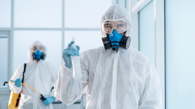 Giovane disinfettante maschio con una bottiglia di antisettico in piedi nella stanza. concetto di tutela della salute.
