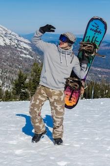 Snowboarder maschio giovane che tiene lo snowboard contro il fondo della montagna