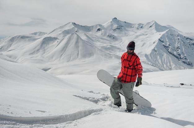 Giovane snowboarder maschio che sta sul pendio di montagna