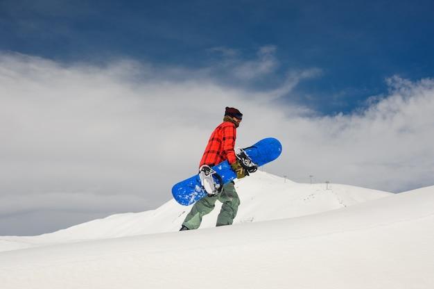Giovane snowboarder maschio che cammina sulla collina con lo snowboard