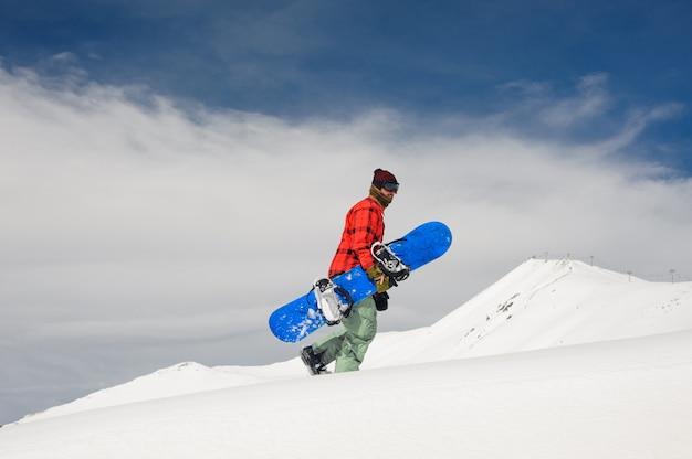 Giovane snowboarder maschio che cammina sulla collina