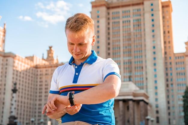 Un giovane studente maschio guarda l'orologio davanti alla principale università russa, il grattacielo di mosca