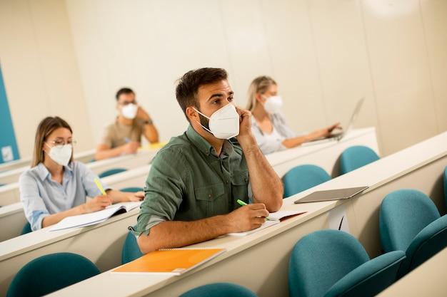 Giovane studente maschio che indossa la maschera medica protettiva per il viso per la protezione da virus in aula