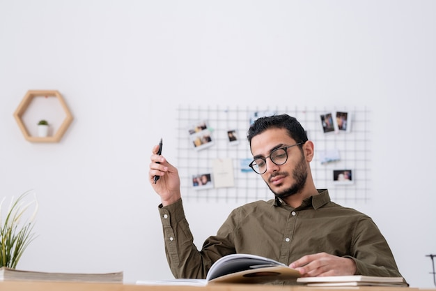 Giovane studente maschio con libro aperto guardando attraverso i materiali di studio mentre si fa i compiti contro il muro bianco